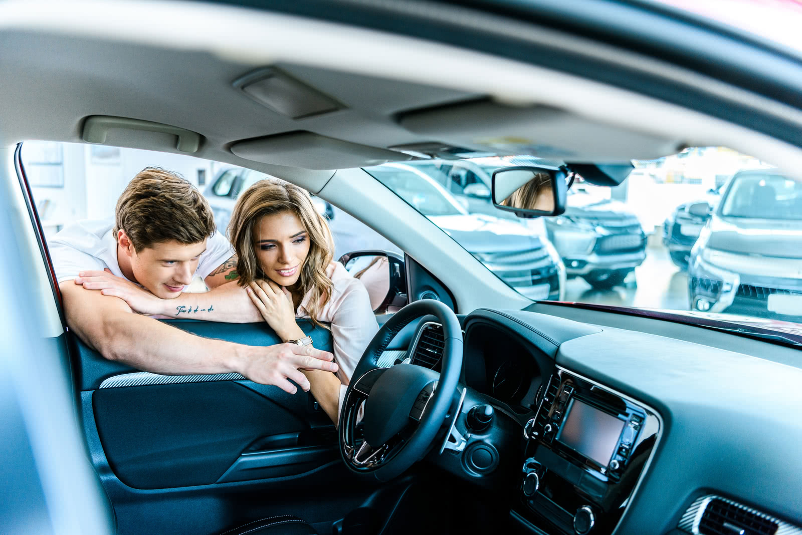 Couple shopping for a new car, signifying loan search process