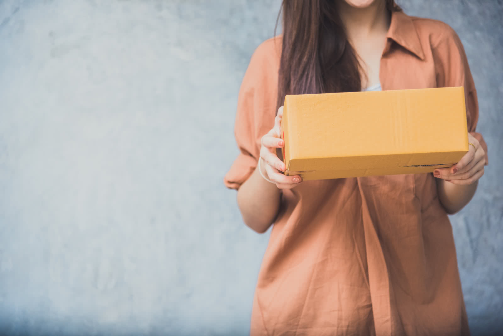 Woman holds a package for customer delivery