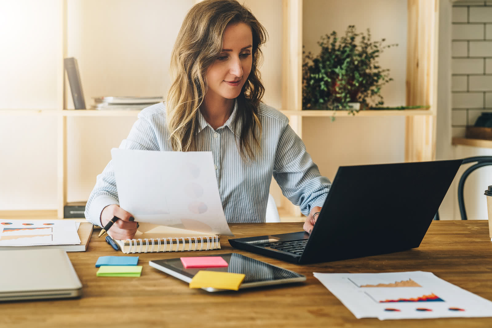 Businesswoman reviewing business metrics on laptop and on paper