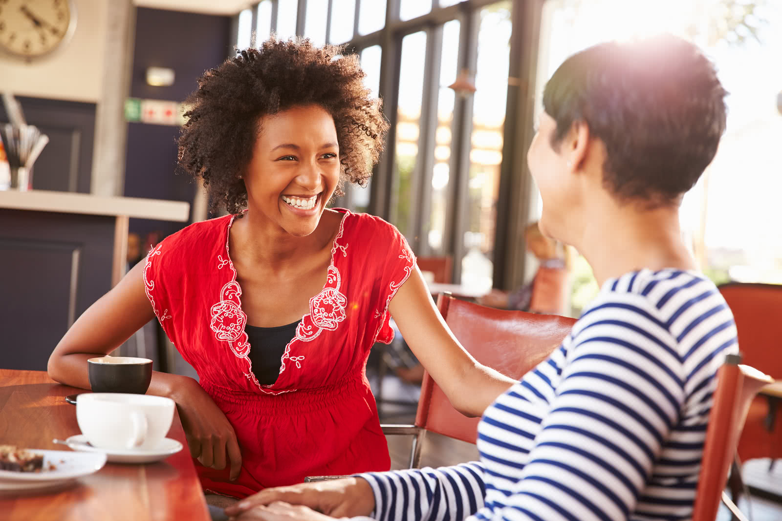 An owner has coffee with a customer on Get to Know Your Customers Day