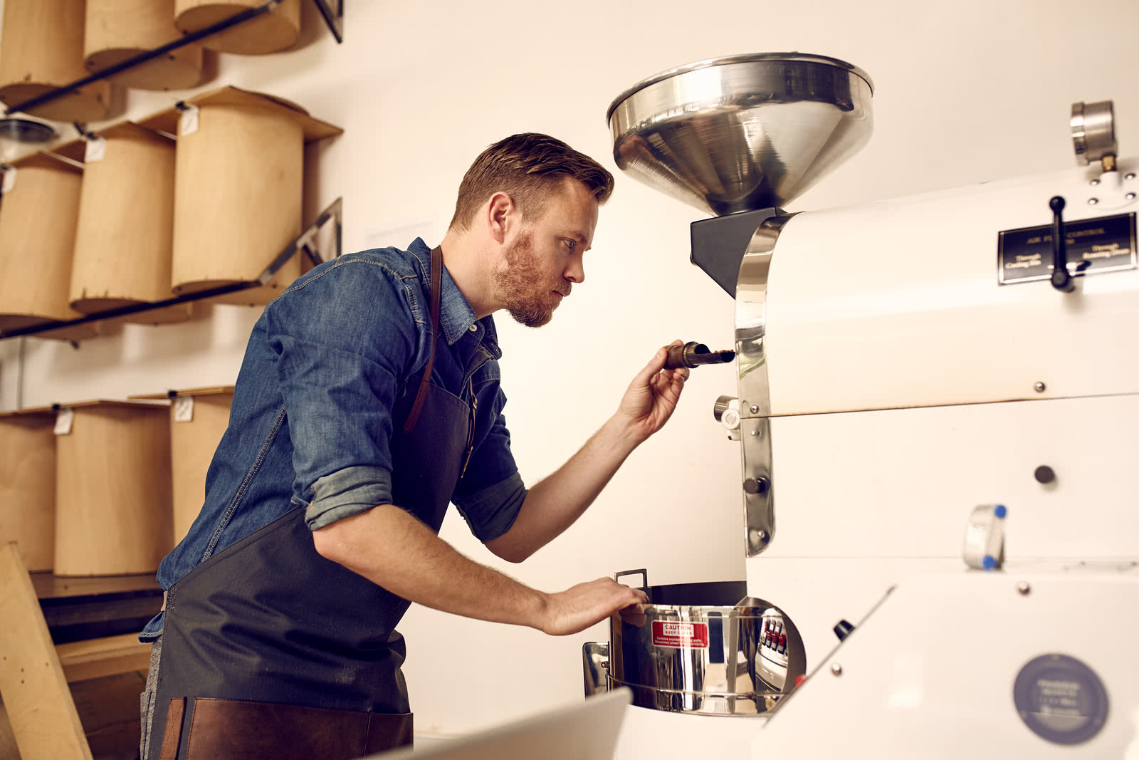 Business owner operating coffee bean roasting machine, purchased using a section 179 tax deduction