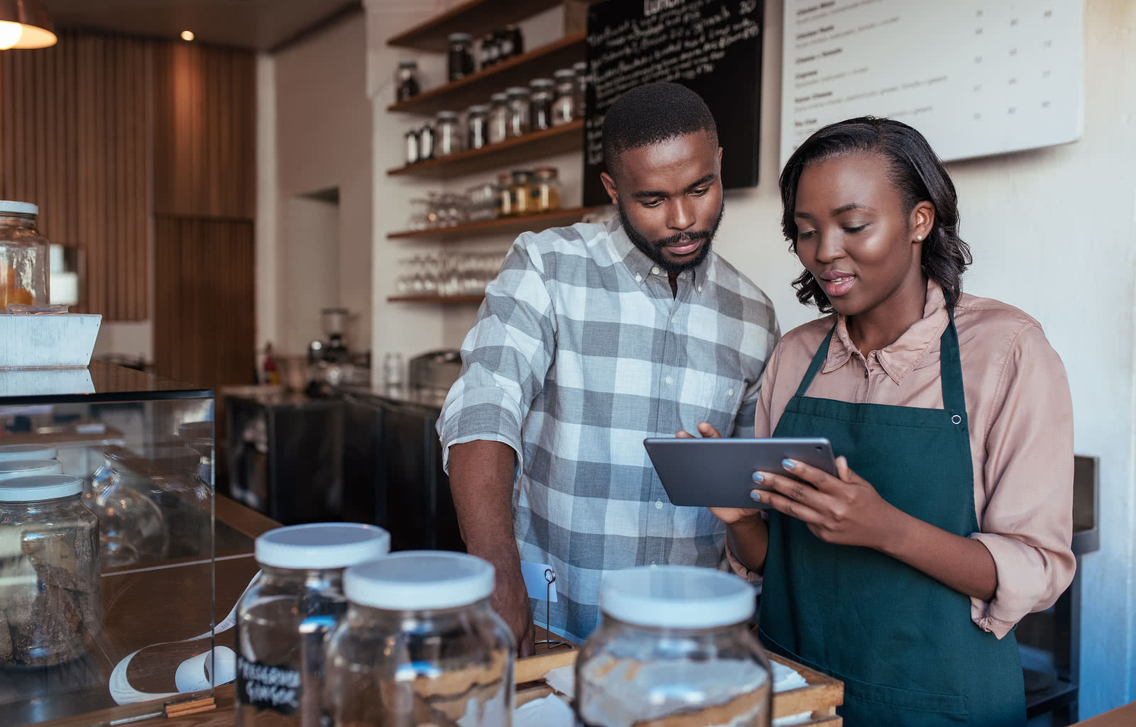 Two business partners use tablet to plan Small Business Saturday ideas for their cafe
