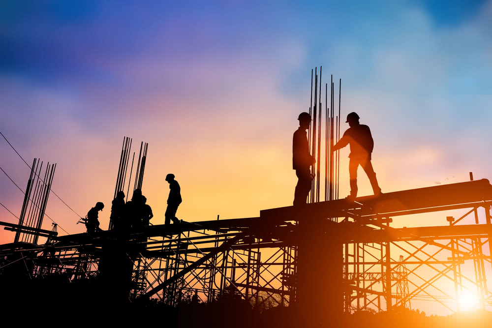 Silhouettes of construction workers on-site on top of a building frame