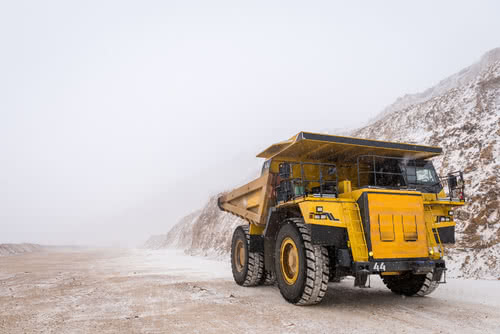 Yellow mining truck drives down snowy road