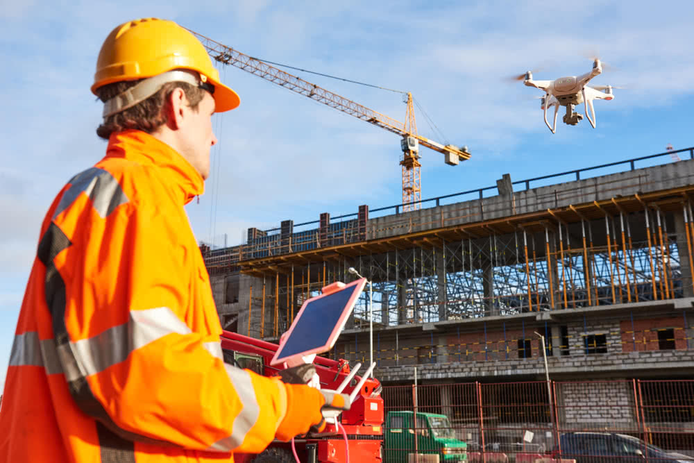 A construction business owner operates a drone on building site, a type of construction technology