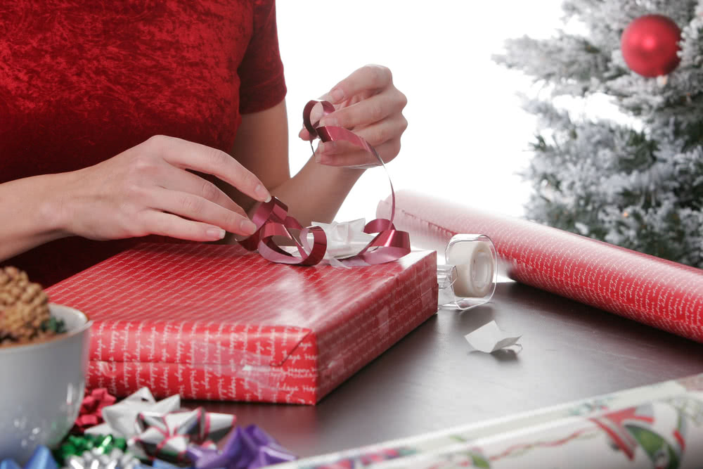 A small business owner wraps employee gifts, which are tax-deductible business expenses