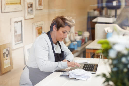 A female deli owner estimates her small business tax preparation cost