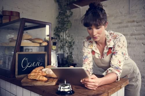 Female small business owner researches women's small business loans to expand her business