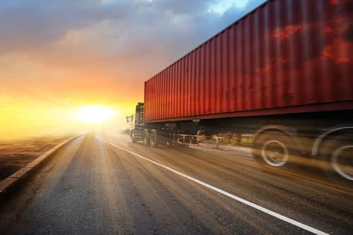 Commercial truck speeding down an empty highway