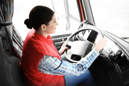 Female landscape company owner drives a truck to a job site