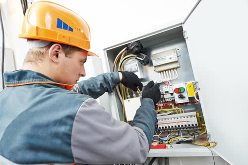 Business owner maintains safety while fixing fuse box, part of how to run a successful electrical business