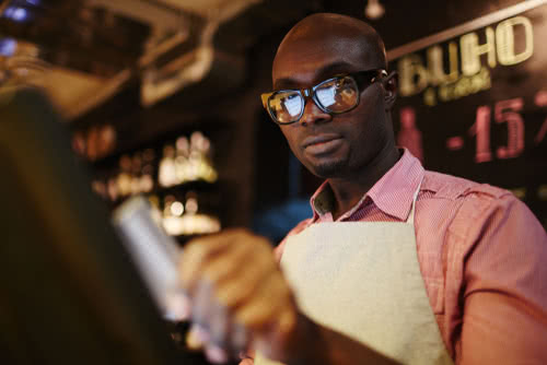 A male waiter in glasses uses a POS system while working in restaurant