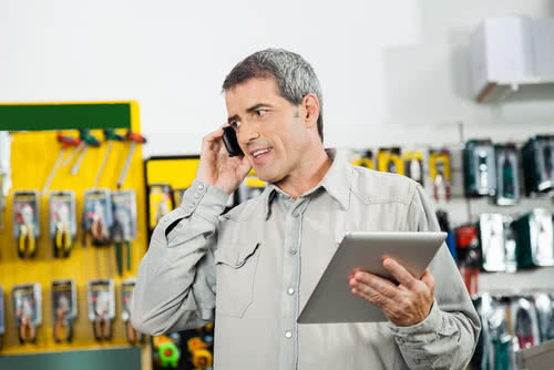 Hardware store owner talks on phone while business automation responds to emails