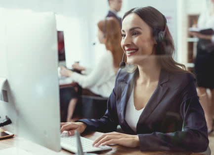 A smiling business owner notes a customer compliment in her small business customer database