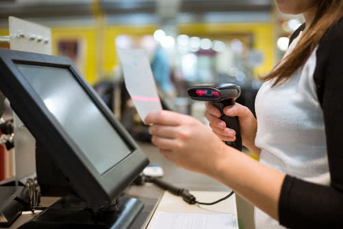 Business owner uses retail POS software to scan bar codes during checkout