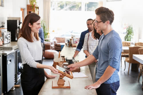 Coffee shop barista at a counter fosters customer loyalty, part of a business contingency plan