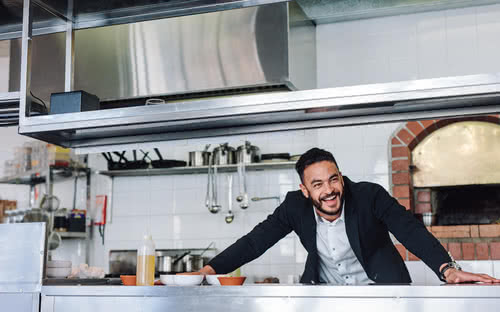 Owner standing in kitchen knows how to run a restaurant successfully