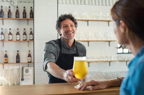 Bartender serves beer to customer, following his bar business plan
