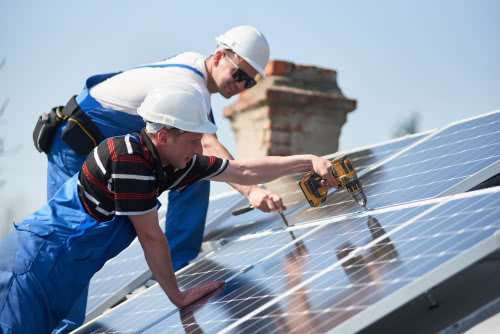Construction workers with green business certification install solar panels