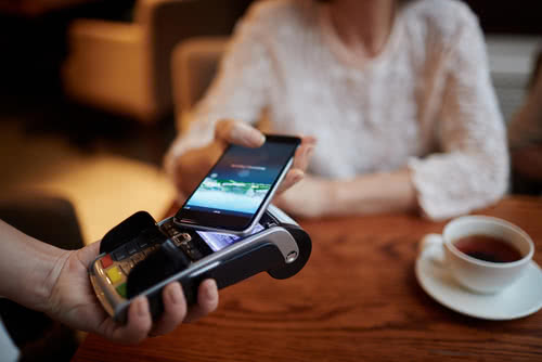 Cafe customer pays with her mobile phone, a small business trend for 2020
