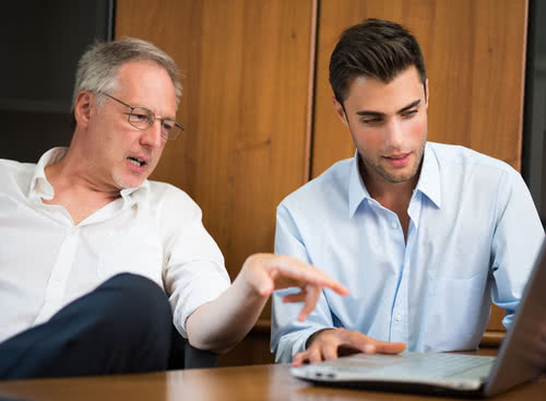 Father and son discuss how to transfer business ownership to a family member