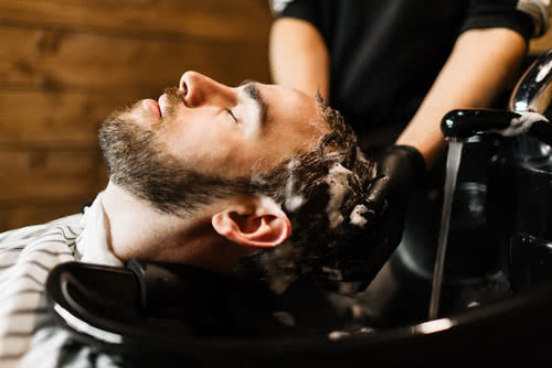 An owner with a salon business plan washes new client's hair