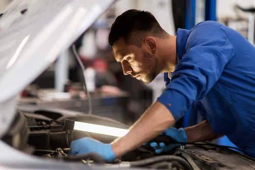 Auto mechanic follows government safety regulations for small business.