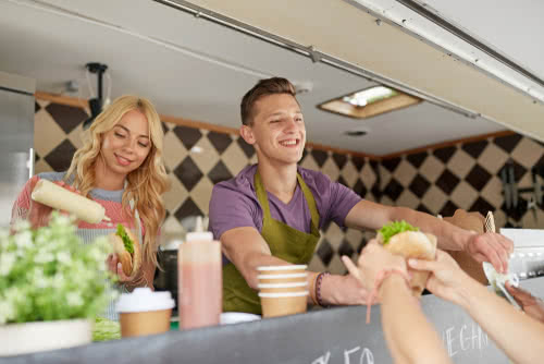 Two food truck owners collect payment with the best finance apps for small business