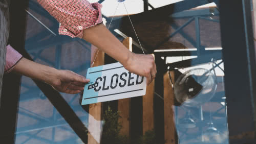 business owner turns sign to closed during coronavirus
