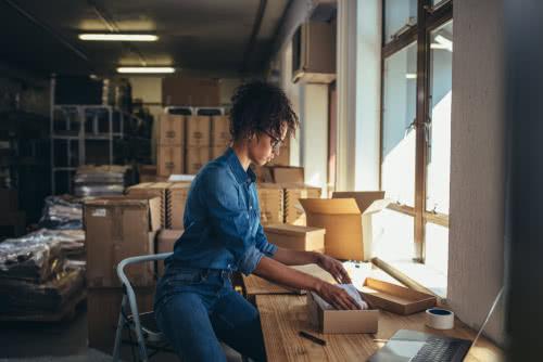 Female business owner reviews paperwork in her storage room