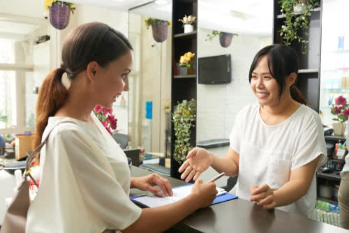 owner of beauty business greets a client
