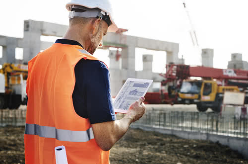 A contractor works on a tablet at job site