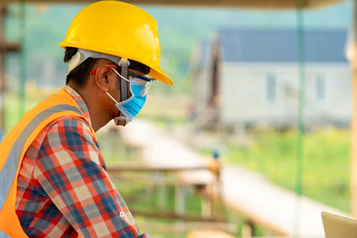 Construction worker wears mask to protect against COVID-19 on a job site