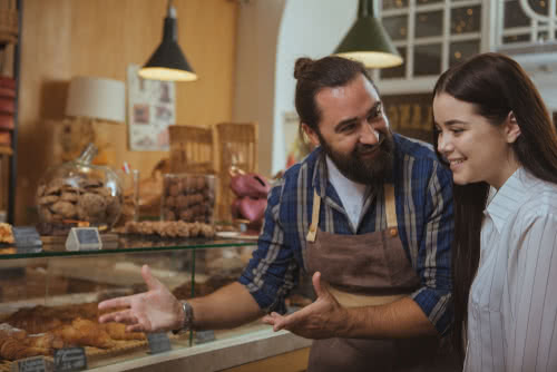 A baker and customer discuss the bakery's referral bonuses=