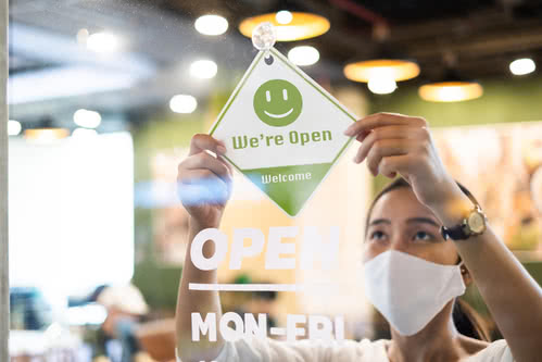 Business owner wearing a face mask puts up the open sign at her business.jpg