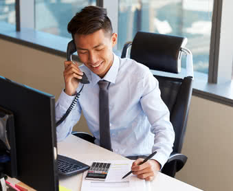 Business owner making phone call sitting at desk in office