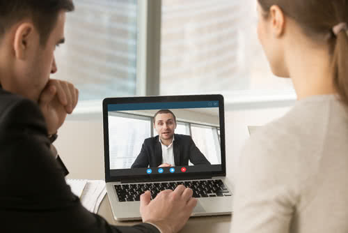 Two remote workers on a video call with a coworker