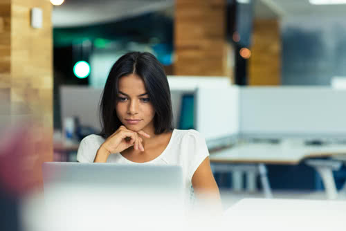 A businesswoman looks thoughtfully at her laptop, protected by cybersecurity for small business